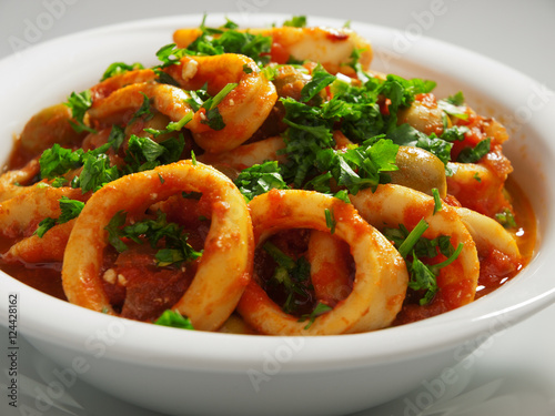 Photo: Calamari stewed in tomato and onion sauces with olives, topped ...