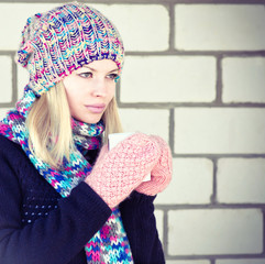 Young Woman with cofee cup Winter time wearing knitted sweater, hat and scarf with mittens Lifestyle concept trendy colors with white brick wall on background