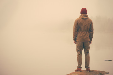 Young Man standing alone outdoor with foggy scandinavian nature on background Travel Lifestyle and melancholy emotions concept film effects colors Wall mural