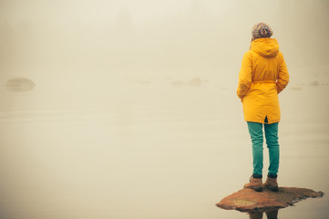 Young Woman standing alone outdoor Travel Lifestyle and melancholy emotions concept  winter foggy nature on background  Wall mural