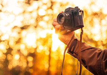 Man hand holding retro photo camera outdoor hipster Lifestyle with sun lights bokeh autumn nature on background