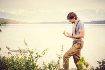 Young Man reading book and writing notes outdoor with scandinavian lake and mountains on background Education and Lifestyle Travel concept