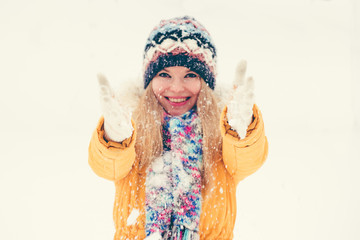 Young Woman wearing hat and scarf happy smiling playing with snow outdoor enjoy winter  vacations Lifestyle