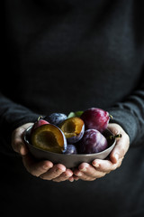 Hands holding a bowl of fresh plums