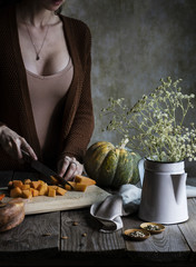 Woman cutting fresh pumpkin on a rustic wooden table