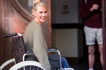 woman in wheelchair in front of entrance door