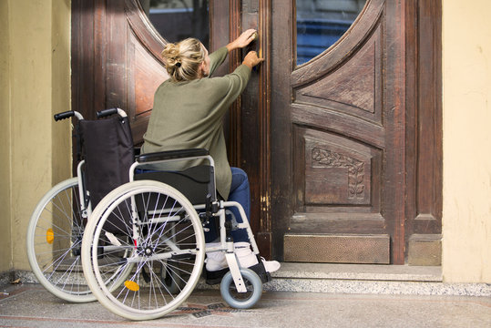 woman in wheelchair trying to get through a door