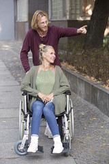 woman in wheelchair and young man showing her something