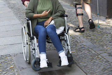 woman in wheelchair pointing to another disabled person