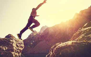 Running Man on Mountains jumping cliff over lake Skyrunning sport Lifestyle Travel concept outdoor