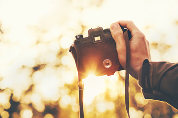 Man hand holding retro photo camera outdoor hipster Lifestyle with sunset lights autumn nature on background