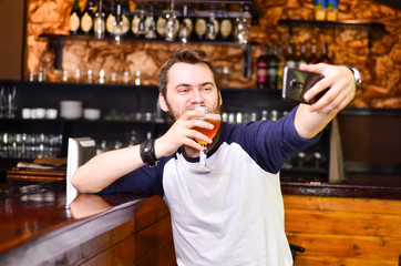 The guy makes selfie with beer in hand
