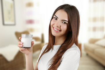 Young woman with glass of milk on blurred interior background.