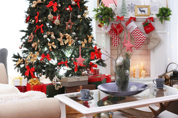 Interior of beautiful living room with fireplace decorated for Christmas