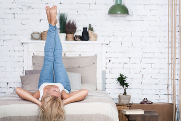 Blond woman with legs up on bed
