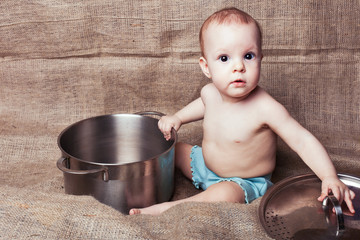 Child girl sits and exploring a pan with surprise