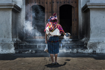 Mayan woman performing a ritual in front of the Santo Tomás church in the town of Chichicastenango, in Guatemala