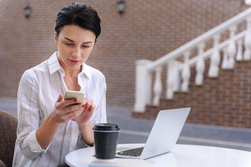 successful woman sitting outdoors with smartphone and laptop