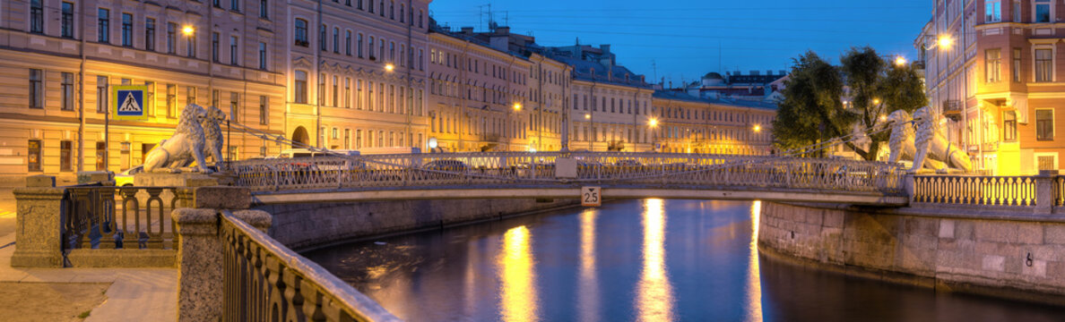 Night view on illuminated Griboedov Canal and Lions Bridge, St. Petersburg, Russia.