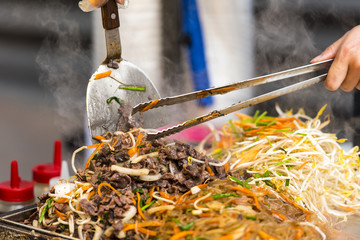 Asian street food - people cooking some food in Seoul - South Korea. Noodle with vegetables and soup