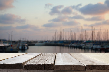 wooden table in front of blurred yachts in pier at sunset