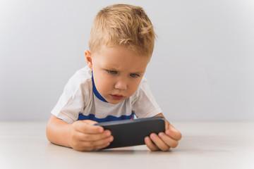 Little boy sitting with digital gadgets in studio