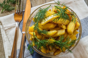 fried potatoes in a glass bowl with dill