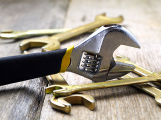 adjustable wrench and a set of open-end wrenches, closeup, shallow depth of field, focus on adjustable wrench head