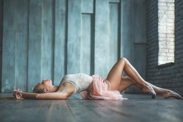 Beautiful ballet dancer lying on floor