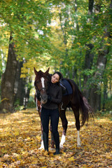 Young attractive girl with white arabian horse in the autumn forest