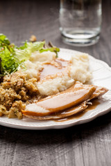 Oven roasted turkey Thanksgiving platter with mashed potatoes, gravy, salad, and stuffing with a cup of water