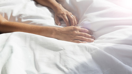 closeup of female hands on white bedsheets