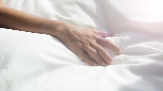 closeup of female arm on white bedsheets