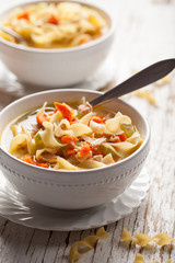 Homemade Turkey Noodle Soup on weathered white wood