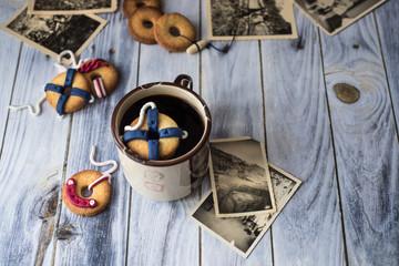 biscotti decorati come salvagenti da nave, uno galleggia in una tazza. Immagine orizzontale con vecchie fotografie ingiallite e alamaro