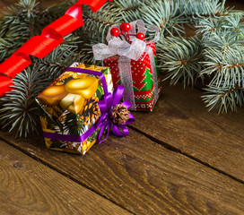 Christmas presents with red ribbon on dark wooden background in