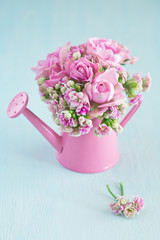 Pink spring bouquet of fresh flowers on a blue background .
