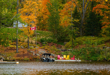 Motor boat and chairs at a cottage dock