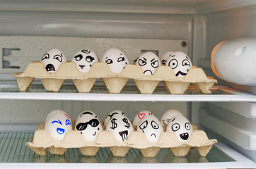 Two trays with painted smiles on the eggs on the refrigerator shelves