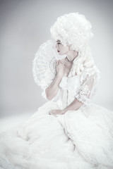 Vintage inspired modern photograph of beautiful woman in a white gown holding a hand fan.