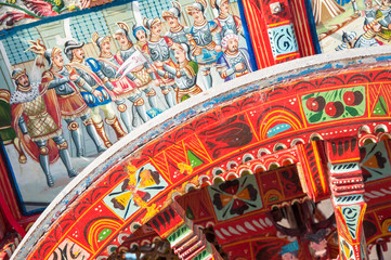Close-up view of a colorful wheel of a typical sicilian cart during a folkloristic show
