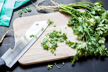 Parsley leaves with a knife on a cutting board