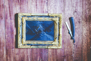 Vintage frame and hairdressing tools on wooden background
