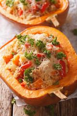Baked pumpkin stuffed with couscous, meat and vegetables close-up. vertical