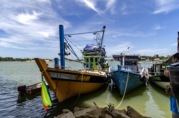 fisherman boat anchored over cloudy and blue sky background at s