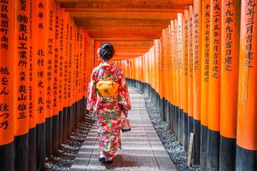 Autocollant pour porte Kyoto Women in kimono stand at Red Torii gates in Fushimi Inari shrine, one of famous landmarks in Kyoto, Japan