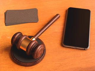 Judge's gavel, smartphone, business card on wooden table. 3D illustration