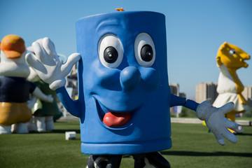 Close up shot of blue mascot character waving at camera