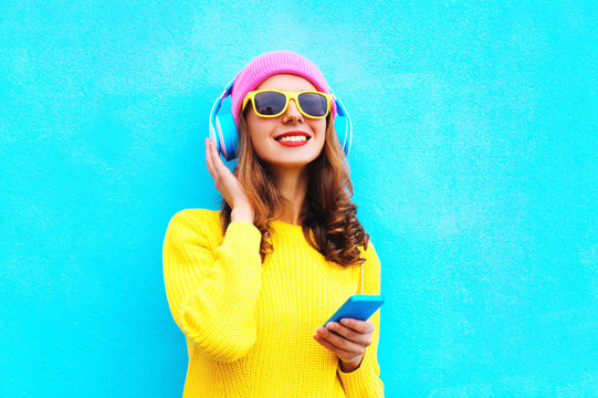 pretty girl in headphones listening to music holds smartphone we