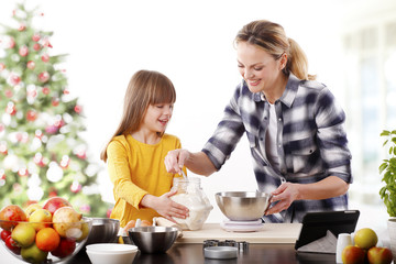 Christmas time. Portrait of cute daughter and her mom baking christmas cookies together in the kitchen.